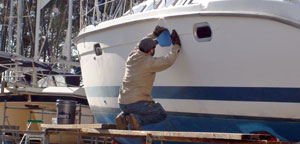 Worker repairing sailboat
