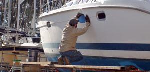 Worker repairing sailboat